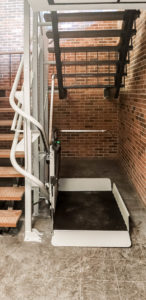 Artira installed in brick building with white stair railings