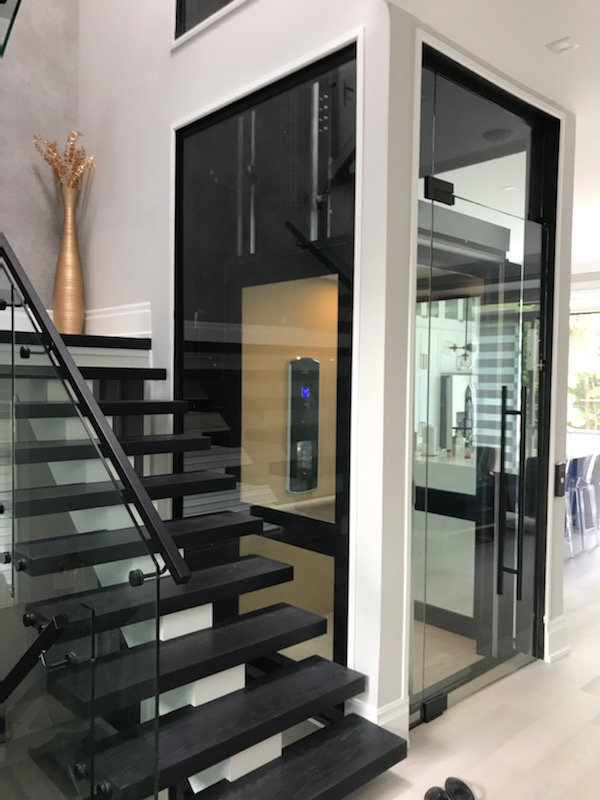 Home Elevator with glass shaft and door in private residence